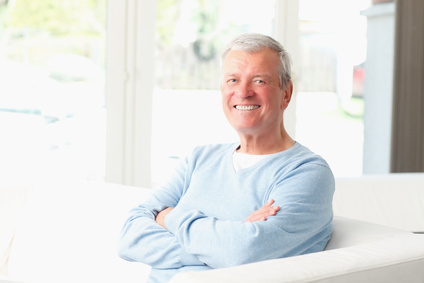 Close-up of active senior man smiling while sitting on sofa at living room.